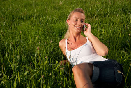 communicates: young woman communicates by phone outdoors Stock Photo