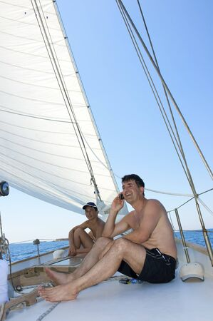 Mature man talking with a cell phone on a sailing boat photo