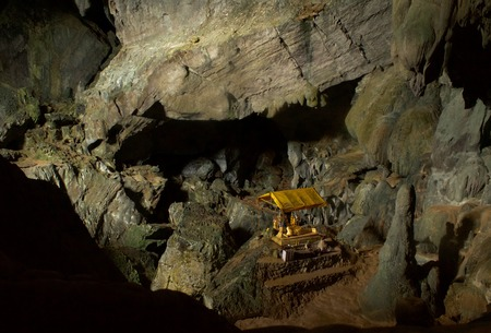 enormous: Enlightenment. Daylight pours in through a large crack in the mountain to illuminate this golden buddha, sleeping peacefully on a golden plinth, inside the enormous entrance cavern of Tham Phu Kham, near the blue lagoon, at the famous traveller paradise o Stock Photo
