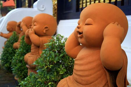 See no evil, hear no evil, speak no evil.  Statues of novice monks at a thai temple convey an age-old concept to visitors. Stock Photo