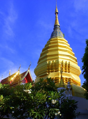 gleams: A tiered-golden stupa reaches heavenward, while behind it, a temple building gleams with golden light from the reflected rays of the sun. At Wat Pan Ping in Chiang Mai city, Thailand.