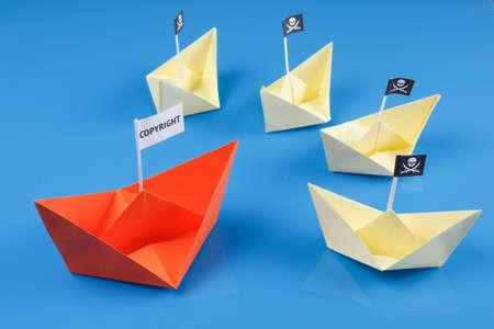 roger: Paper origami ship and several pirate Vessel with black flag Jolly Roger Stock Photo