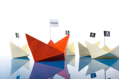 Paper origami ship and several pirate Vessel with black flag Jolly Roger Stock Photo