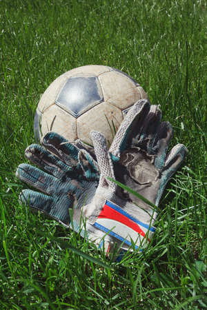 raged: Dirty old soccer ball and goalie gloves on grass