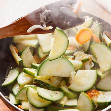 rises: Vegetable ragout. Zucchini and onions with carrots in a pan. steam rises up. Stock Photo