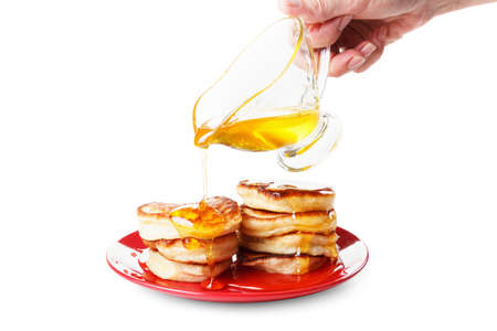 flapjacks: Chef pours sweet syrup, or  honey, on flapjacks. White background