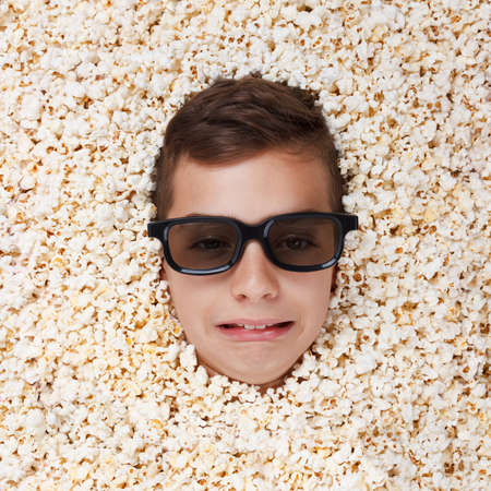 melodrama: Sad crying young boy in stereo glasses watching a movie from popcorn