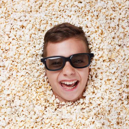 lachendes gesicht: Lachender Junge in Stereobrille einen Film von Popcorn Lizenzfreie Bilder