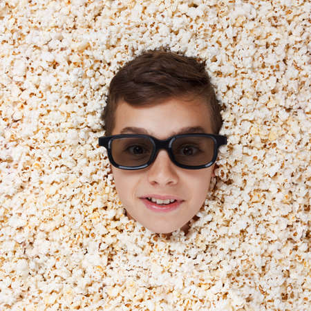 flaunt: Grinning, flaunt young boy in stereo glasses watching a movie from popcorn Stock Photo
