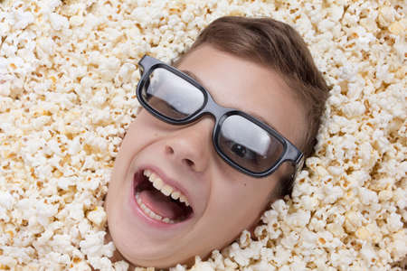talk show: Laughing young boy in stereo glasses watching a movie from popcorn Stock Photo