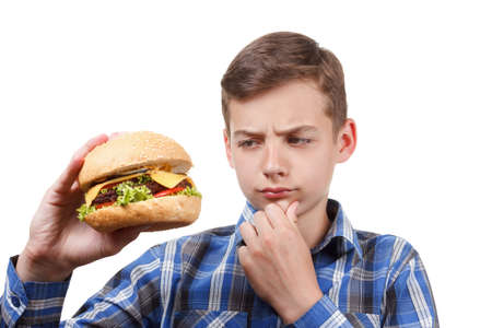 upper half: Boy looks at a cheeseburger and thinking. Indecision, hesitation Stock Photo