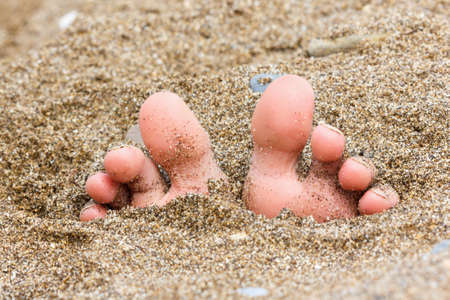 beach feet: toes buried in the sand of the sea on the beach, foot on the sand, summer theme Stock Photo
