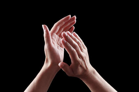 clapping: beautiful female hands isolated on black background giving applause Stock Photo