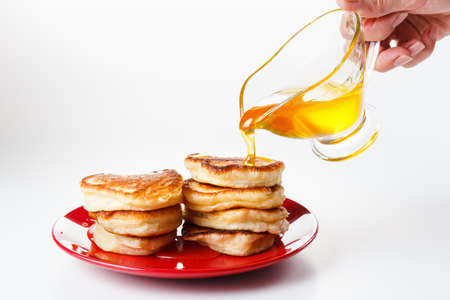 flapjacks: Chef pours sweet syrup, or  honey, on flapjacks Stock Photo