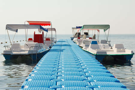 personal watercraft: Floating pier on the beach and empty pleasure watercraft Stock Photo