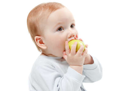 half length: Child eating green apple toys in a blue dress. Studio Half Length Portrait , isolated on a white background Stock Photo