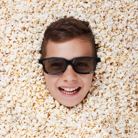 talk show: Smiling young boy in stereo glasses watching a movie from popcorn