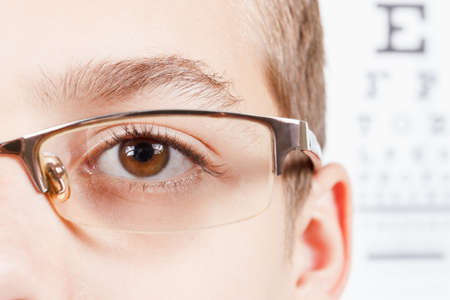 sight chart: Child an ophthalmologist .Portrait of a boy with glasses.  Eye exams. Check Table view. Macro studio shoot profile Stock Photo