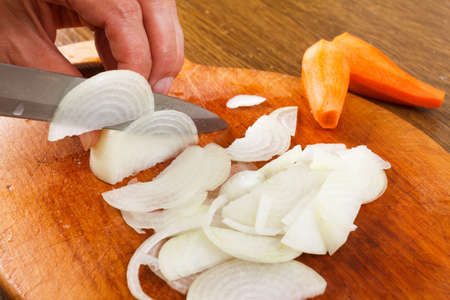 Cut onion on chopping board for cooking