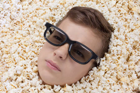 teen boy: serious young boy in stereo glasses watching a movie from popcorn