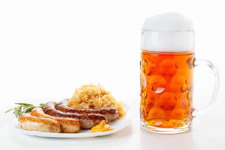 Octoberfest menu, beer mug with foam, a plate of sausages and sauerkraut. Oktoberfest meal.