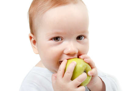 half length: Child eating green apple. Studio Half Length Portrait , isolated on a white background Stock Photo