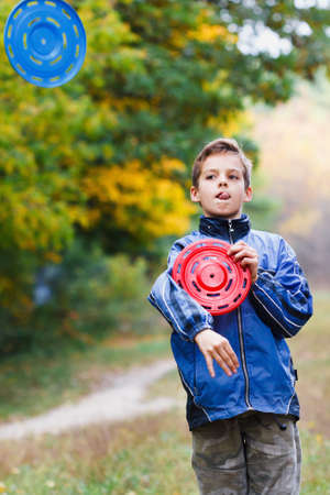 artful: Artful guy with two Frisbee on the background of autumn yellow forest Stock Photo