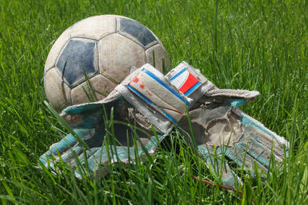 goalie: Dirty old soccer ball and goalie gloves on grass, after the game