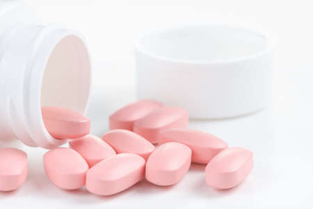 Several pink oval pills poured out of a white bottle on white background. Imagens