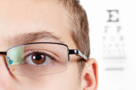 testing vision: Child an ophthalmologist .Portrait of a boy with glasses.  Eye exams. Check Table view. Macro studio shoot profile Stock Photo