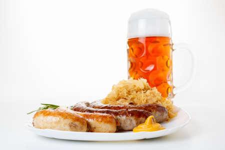 wiesn: Octoberfest menu, beer mug with foam, a plate of sausages and sauerkraut. Oktoberfest meal.