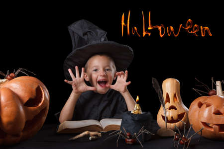 witchery: Child and spooky Halloween pumpkin with magic book, candle, spider isolated on black background Stock Photo