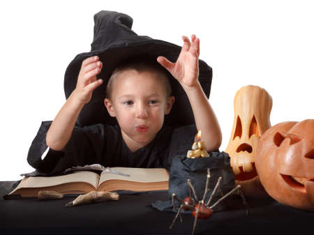 enchantment: Child and Halloween pumpkin with magic book, candle, spider. Isolated on white background