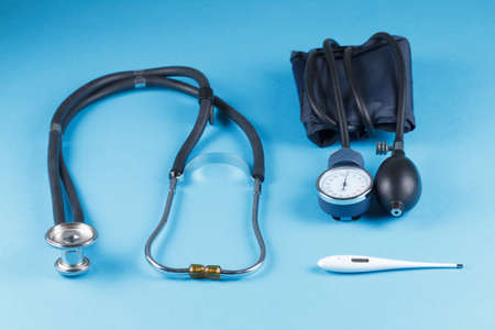 tonometer: Medical devices stethoscope, tonometer, and thermometer on blue background