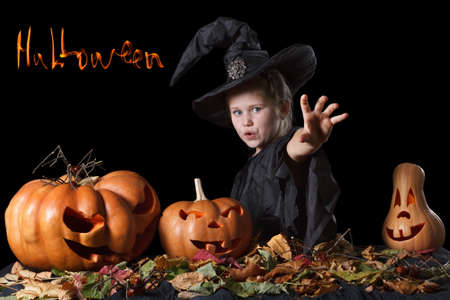 to curse: Halloween. Wicked witch casts a spell and sends the curse. Surrounded scary pumpkins and leaves on a black background
