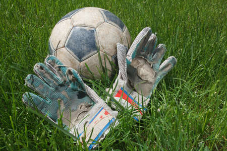 raged: Dirty old soccer ball and goalie gloves on grass, after the game