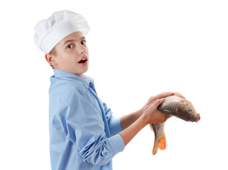 cypriniformes: Young caucasian chef holding a fish carp. Cooking wholesome food. Isolated on white background Stock Photo