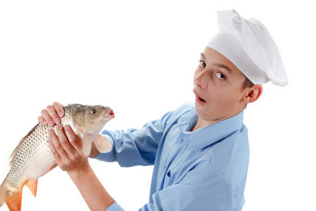cypriniformes: Young chef holding a fish carp. Hilarious cooking wholesome food. Isolated on white background Stock Photo