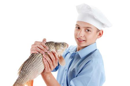 cypriniformes: Young caucasian boy holding a fish carp. Hilarious cooking wholesome food. Isolated on white background Stock Photo