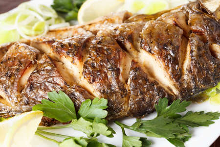 christmas meal: Baked carp fish with vegetables entirely. Traditional Christmas meal. Closeup Stock Photo