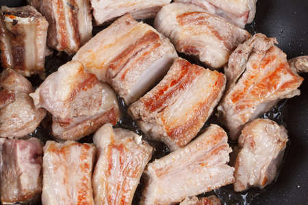 cook griddle: Roasted pork ribs in oil on a black frying pan Stock Photo