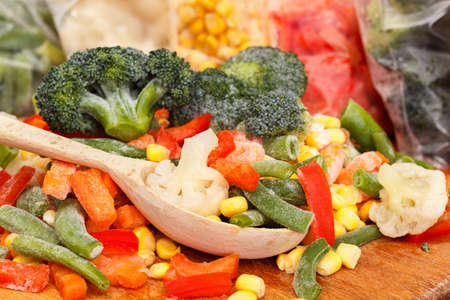 Mixed frozen vegetables on cutting board and plastic bags close up