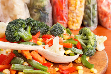 Mixed frozen vegetables on wooden cutting board and plastic bags Imagens