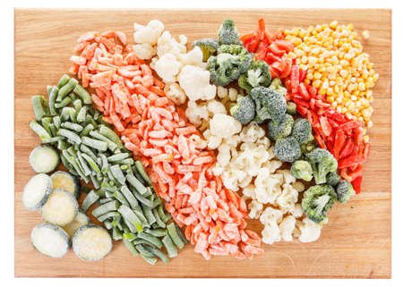 Mixed frozen vegetables on cutting board. Isolated on white background
