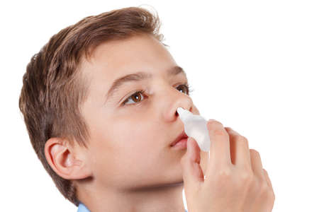 nose drops: Boy drips medical nose drops for quick recovery. Isolated on white background