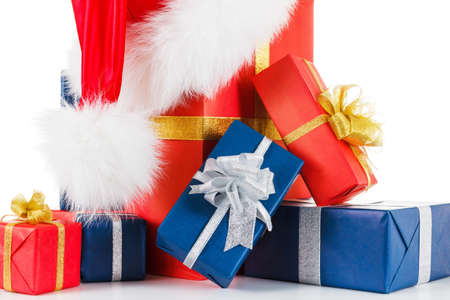 Fur hat santa hat with gift boxes. Silver and gold ribbons. Isolated on white background closeup