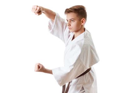 martial: Martial art sport karate - child teen boy in white kimono training karate punch and block