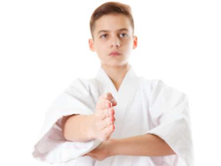 Martial art sport karate - child teen boy in white kimono training karate punch and block