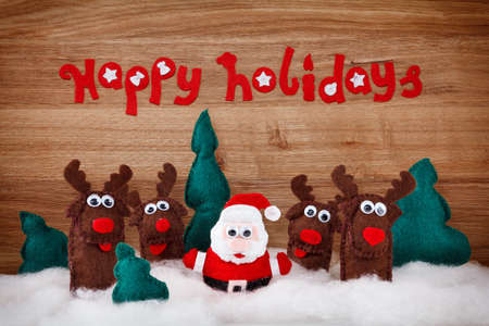 happy holidays: Christmas deer and Santa Claus. The concept of Xmas soft toys made of felt in the snow on a wooden background with the words - Happy Holidays Stock Photo