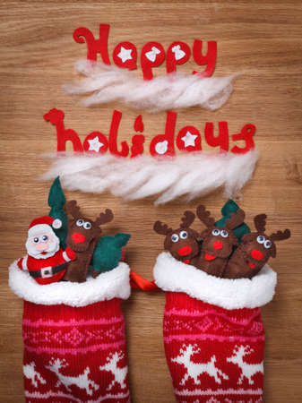 fireplace family: Christmas Fireplace, Family Socks, Xmas snow Decoration, Santa and deers. Words Happy Holidays on wooden background Stock Photo